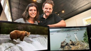 Portrait of Tiffany and Tim Sears with monitors displaying their live web cam views of bears at Brooks Falls at Katmai National Park in Alaska, at left, and ospreys at Hog Island in Bremen, Maine. — Charlie Neuman UTSanDiego